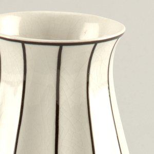 White baluster vase with thin black vertical stripes.