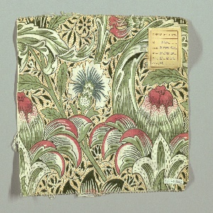 Large-scale design of cornflowers and artichoke-like flower heads on curving stems in pink, greens, blue, white and dark green outlines, on a white ground with yellow dots and all-over pattern of dark green scrolling stems and leaves.