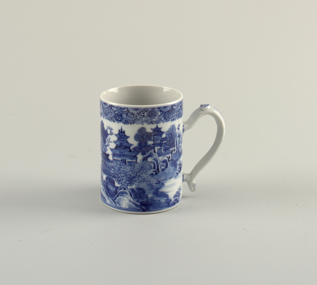 Mug with loop handle; Chinese landscape in blue on white ground. Upper rim decorated with floral band.