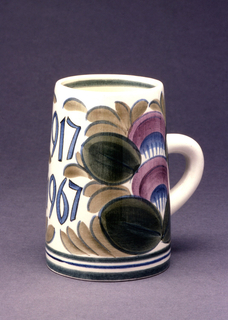 """Cylindrical, slightly narrower towards top, loop handle; polychrome glazed decoration with """"1917/1967"""" inscribed opposite handle amid stylized flowers and foliage."""