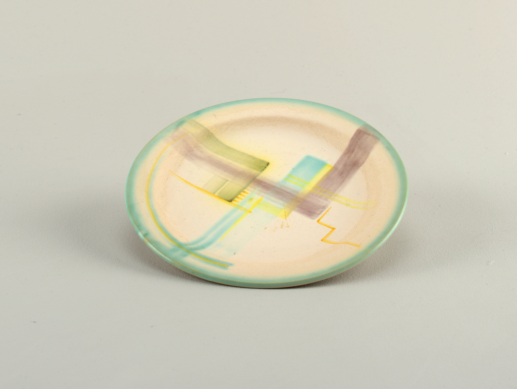 Plate decorated with brushed lines in tan, yellow, black and turquoise; turquoise around the rim.