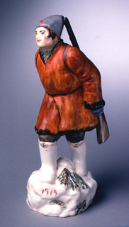 """Man dressed in boots, heavy jacket, hat, with gun hung over shoulder, in striding pose; in relief on base """"1919."""""""