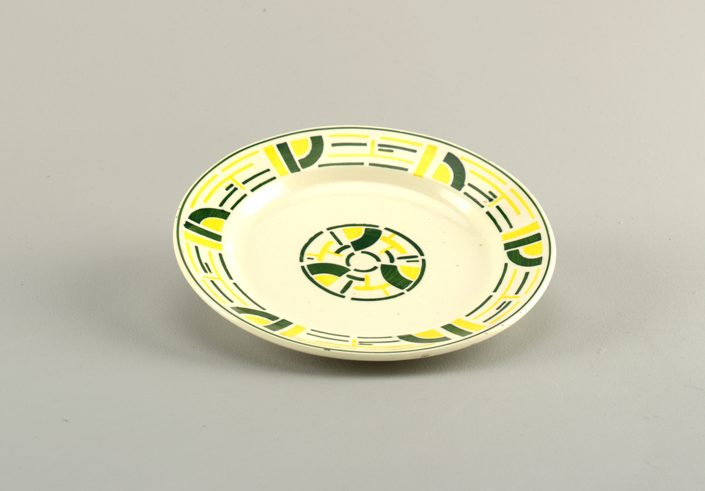 Circular plate with raised bottom rim and slanting edge leading to a concave center.  White background with abstract yellow and green designs around the edge.  Central design of a green circle containing yellow and green lines, bands, and partial circles.