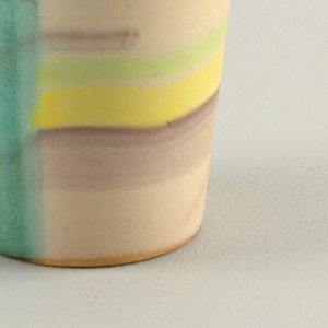 Straight slightly flared beaker decorated in geometric shapes in turquoise, yellow and gray.