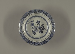 Circular bowl with wide rim; painted in underglaze blue with dark outlines (trek), in center with chinoiserie bird and floral spray, around the rim with floral border; on back several rings of blue and trek circled around foot rim.