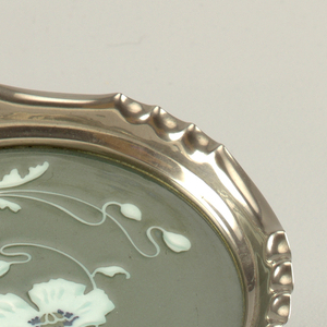 Round with scrolling floral design in white and pale green against a grey-green ground. Metallic rim with divots.