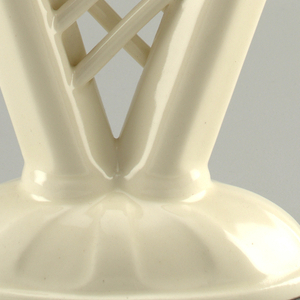 Domed base with two candlesticks connected by six crossing bands. Creamy white glaze.