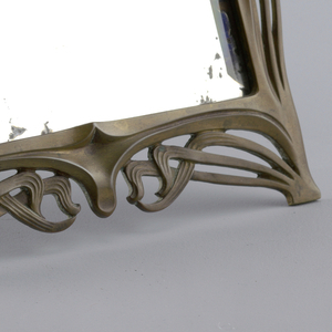 Rectangular mirror with shaped, open-work brass frame. Easle-type support on reverse.