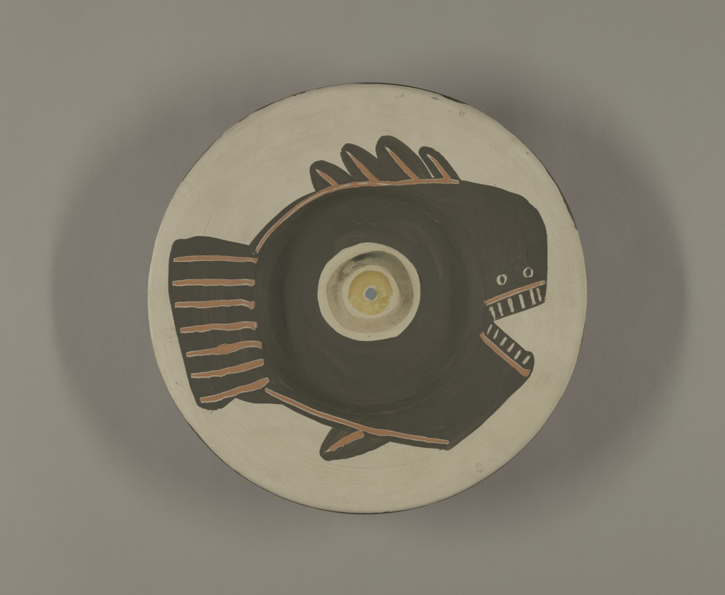 "Round plate decorated with the design of a large abstract fish whose eye is centered in the well. Engobe decoration on red clay. First coat white, over this the fish - a flat black shape with fin characteristics made by wide incised lines exposing clay. Eye is a greenish circle surrounding a yellow pupil with a blue iris. Underside: colors and order of application the same a stop. A black ribgon one-half the radius descriibes the rim of a wheel. Five white cartouches in this plane, four sun-faces motifs and one inscribed: ""16.4.5F."""