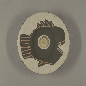 """Round plate decorated with the design of a large abstract fish whose eye is centered in the well. Engobe decoration on red clay. First coat white, over this the fish - a flat black shape with fin characteristics made by wide incised lines exposing clay. Eye is a greenish circle surrounding a yellow pupil with a blue iris. Underside: colors and order of application the same a stop. A black ribgon one-half the radius descriibes the rim of a wheel. Five white cartouches in this plane, four sun-faces motifs and one inscribed: """"16.4.5F."""""""