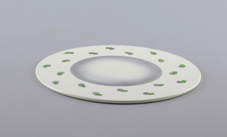 Flat circular form, the white ground with geometric decoration of small overlapping green rectangles and grey discs dispersed around a central airbrushed grey-to-white circle.