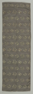 Panel, possibly an obi fragment, has a ground of dark gray patterned with small-scale circular motifs of cranes and dragons in gold, silver, green, brown, and purple.