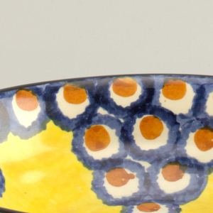 Stepped circular bowl on prong feet. Yellow glaze rimmed in black with interior circular pattern in blue and orange.