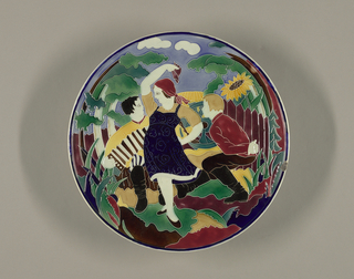 Large, circular, with scene of three figures--man playing accordion, man and woman dancing--in pastoral setting. Glazes predominantly green, red, yellow, separated by cloisonne-like ridges.