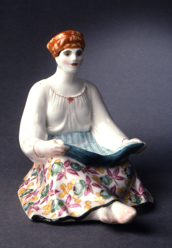 Woman seated, holding out apron, wearing red head kerchief, flowered skirt.