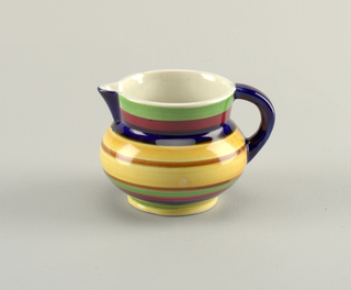 Squat globular form with loop handle opposite triangular spout. The exterior decorated with concentric bands of underglaze green, blue, yellow, red and brown; blue spout and handle; white interior.