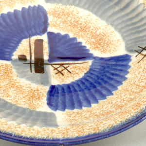 "Asymmetrical plate appearing as if two semi-circles were joined together about one inch off sides, with raised bottom rim and flat top edge.  White background speckled with orange.  Edge lined in deep blue.  Abstract pattern consists of ""lined"" patches of blue and gray.  Four areas of brown crossed lines.  Centered opposite quarter circles, one of blue and one of gray."