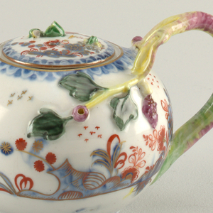 Globular teapot with vine form handle extending onto the body of the teapot with applied grapes and leaves.  The sides are decorated with Imari style trailing flowers below, a blue scalloped border at top. The matching lid applied with branch form handle (broken).