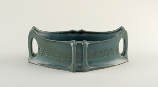 """Oval in plain, tepering toward ends to create """"boat-shape"""". At each end a molded, ribbed, handle with oval piercing; the handles continuous with the concave body wall. Paired supplamentary ribs at each side center continuous with lip. each side of body molded with decorative band of three parallel wavy lines between double row of small bosses. Exterior and interior glazed with mottled blue-green."""