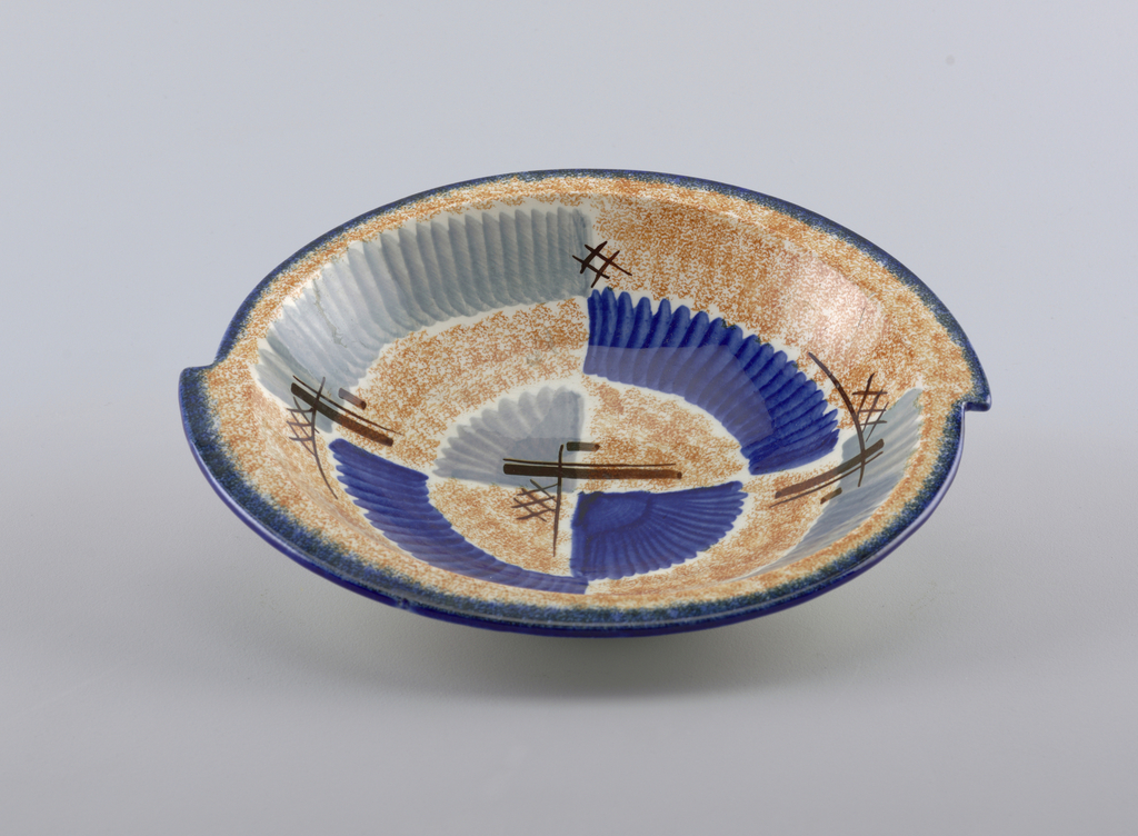 "Asymmetrical bowl appearing as if two semi-circles were joined together about one inch off sides, with raised bottom rim and flat top edge.  White background speckled with orange.  Edge lined in deep blue.  Abstract pattern consists of ""lined"" patches of blue and gray.  Four areas of brown crossed lines.  Centered opposite quarter circles, one of blue and one of gray."
