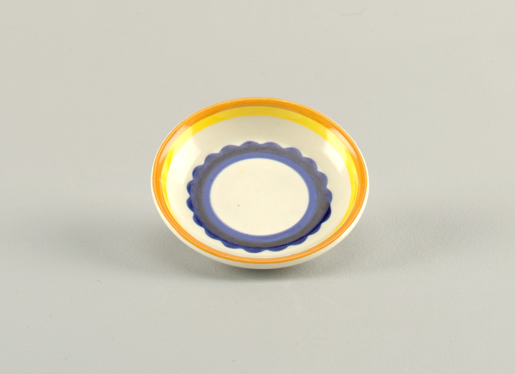 Circular concave dish.  Cream background with concentric circles from edge to center of : orange, yellow, cream, royal blue with a scalloped edge, dark blue, royal blue, and finally a round cream center.