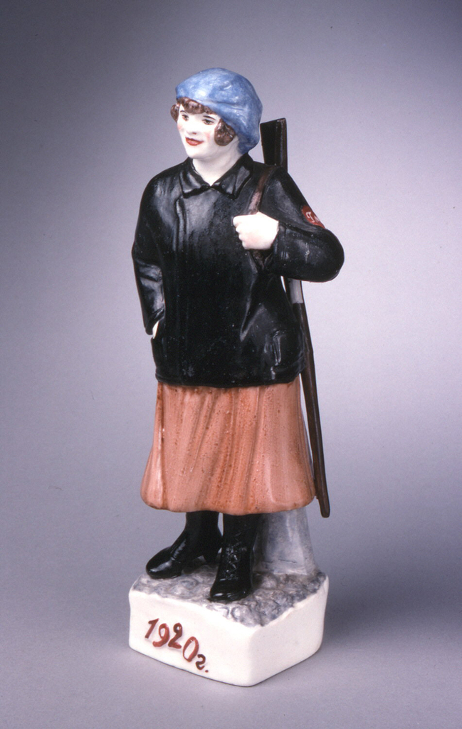 """Young woman standing, holding rifle strapped over left shoulder, her right hand in pocket of jacket; she stands on base with raised inscription """"1920."""""""