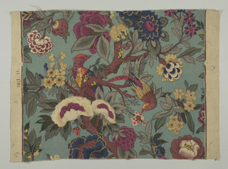 Multicolored block printed fabric on a blue-green ground has serpentine branch with green leaves and large exotic flowers in shades of lavender, blue and yellow. A pair of exotic birds in brown, lavender and blue with red crests perch on branches.