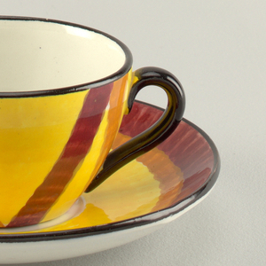 Circular cup narrowing at the bottom with a heart-shaped handle on the side.  Handle and rim painted black.  Yellow background with stripes of orange and burgundy.  Circular saucer with raised bottom rim.  Top edge outlined in black. Surface patterned with concentric circles of: burgundy, orange, yellow, and a round white center.