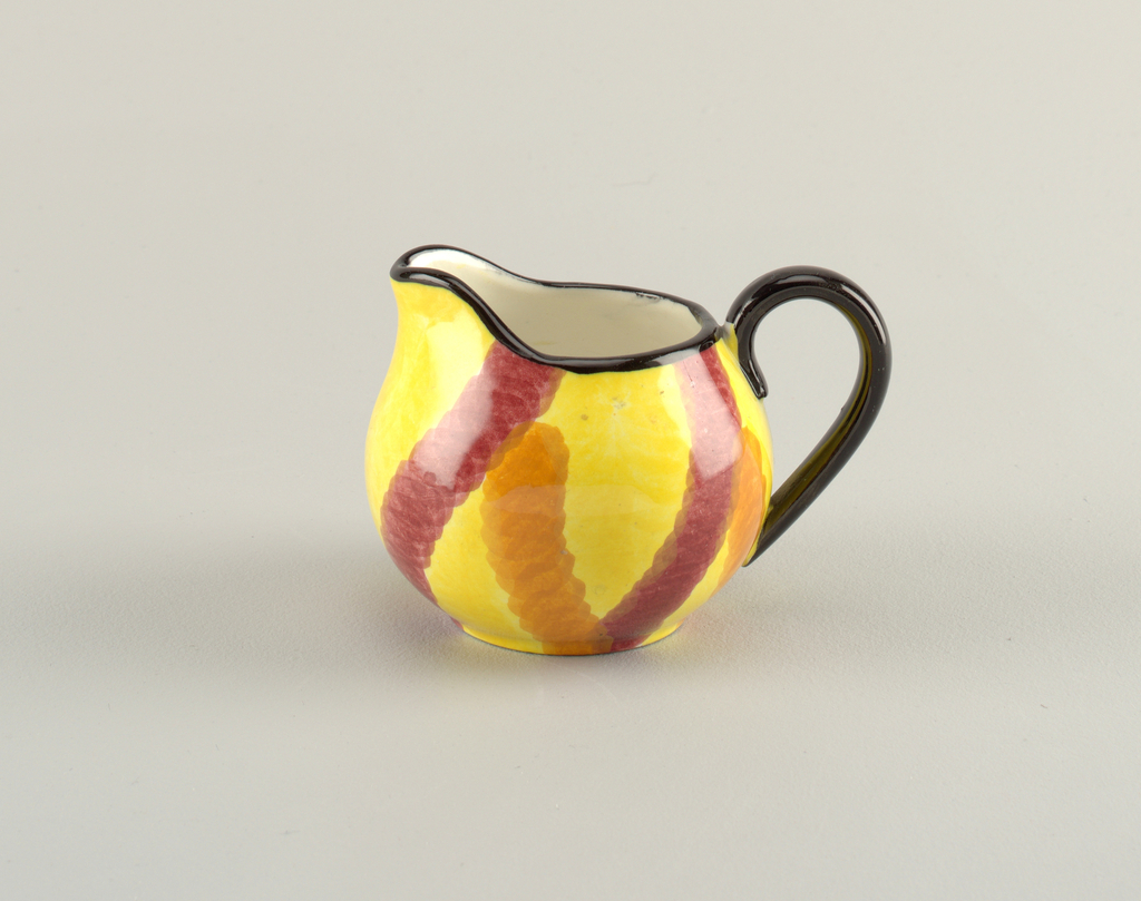 Circular body with a c-shaped handle and curving lip.  Upper edge and handle both painted black.  Yellow background with connected, irregular stripes of orange and burgundy.