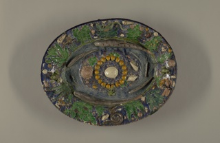 Oval platter in the style of Bernard Palissy. Entire surface decorated with molded and applied leaves, shells and sea creatures. At center, a circle of shells surrounded by waving lines indicating water.