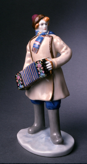 Young man dressed in hat, muffler, fur-lined jacket, boots, standing, hold-ing accordion ornamented with floral decoration.