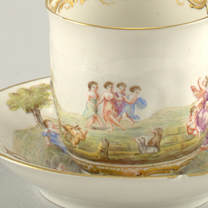 Curved, tall cup, with slightly flaring edge. Saucer curved. Figures and animals in landscape in polychrome relief on both cup and saucer. Scrolled band on base and inner edge of cup. Gold rim.