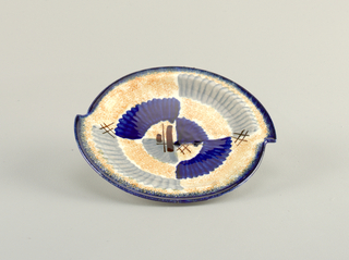 Asymmetrical plate appearing as if two semi-circles were joined together about one inch off sides, with raised bottom rim and flat top edge.  White background speckled with orange.  Edge lined in deep blue.  Abstract pattern consists of striped patches of blue and gray.  Four areas of brown crossed lines.  Centered opposite quarter circles, one of blue and one of gray.