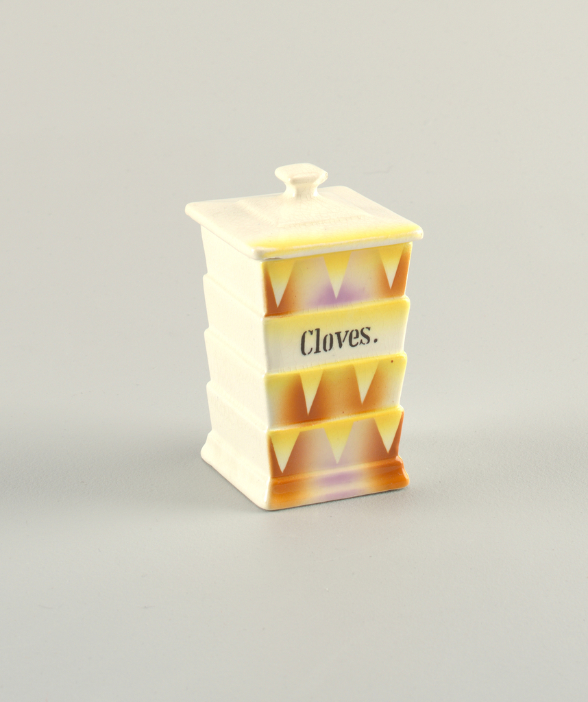 High rectangular box with shallow steps on all sides. Unpainted, except on one side, which shows atomized orange and yellow decoration and triangles. Stenciled text in black: Cloves. Square knob on lid.