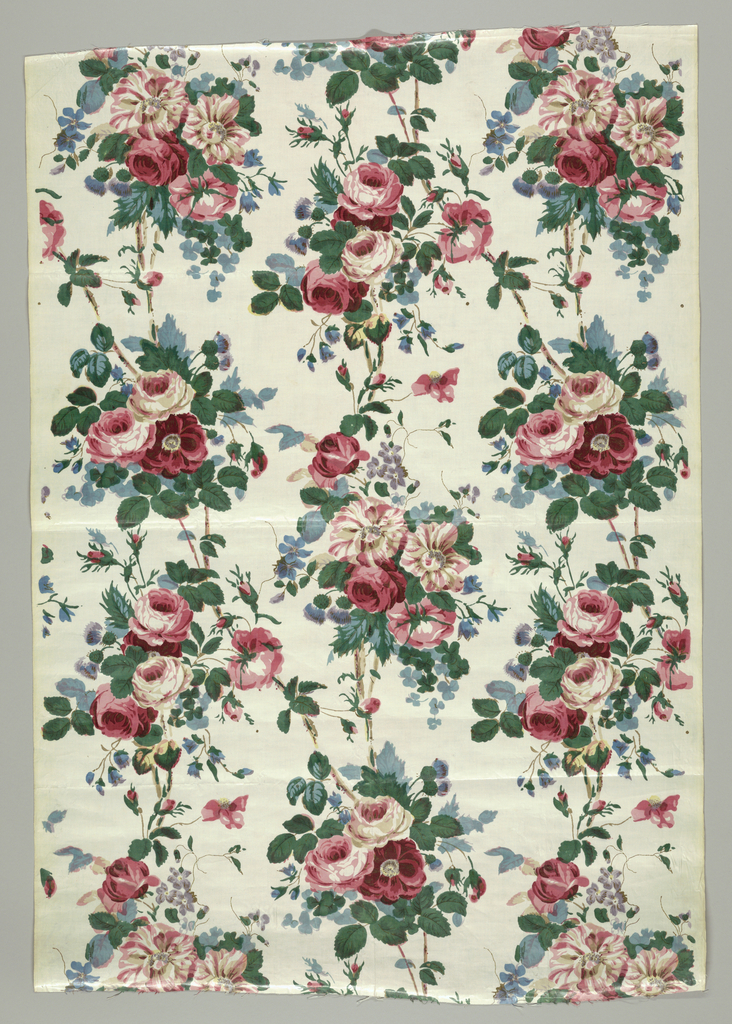 Panel of glazed chintz with a white ground showing a design of roses and other flowers in clusters in a perpendicular arrangement which is well disguised by joining tendrils. In shades of red, green, blue, lavender, dark brown, and touches of yellow.