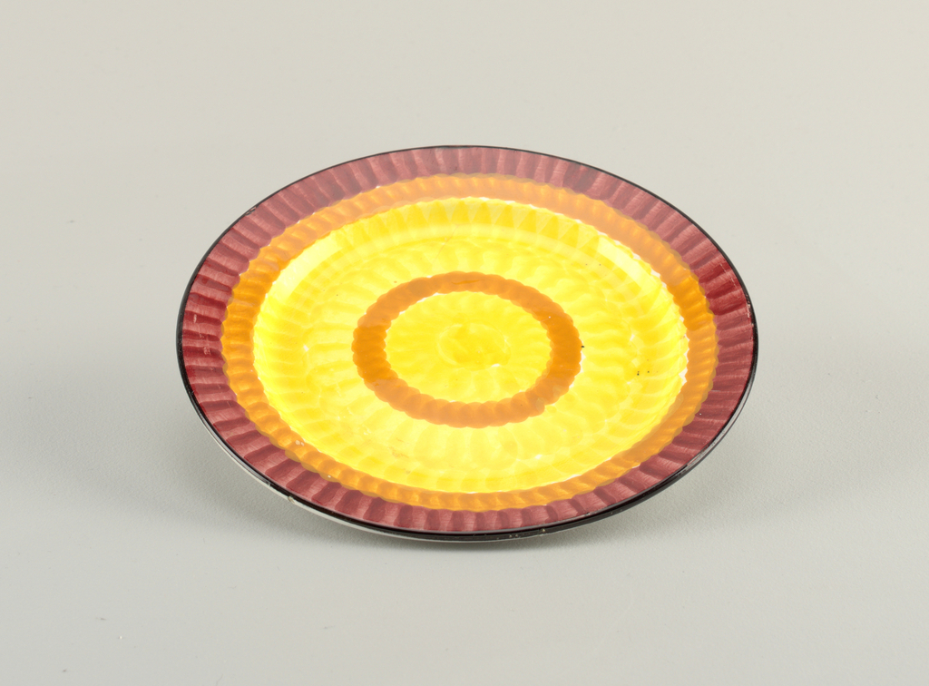 Circular plate with raised bottom rim and slightly concave center.  Black outside edge with interior concentric circles of: burgundy, orange, a wide yellow, orange, and finally a round yellow center.