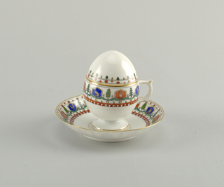 On flaring foot an egg-shaped cup and knob-less cover; angular handle.  Curved saucer.  Both the cup and saucer are decorated with red and blue hexagonal cartouches with animals. Between the cartouches are green trees, above red stars and below, yellow trees and a red line with dents.