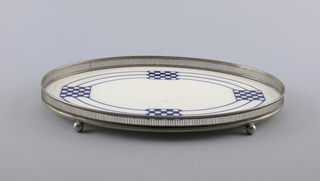 Oval ceramic plaque set in silvered metal frame with upright gallery rim; four ball feet.  Plaque ornamented with four checkerboard squares joined by three large oval rings.