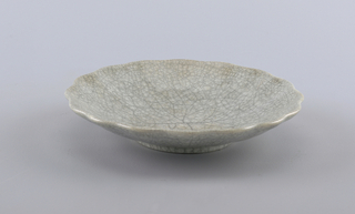 Circular concave form with molded scalloped edge and undulating sides.  Entire surface covered with a gray crackle glaze.  Thin black lines run like spider webs over the surface.