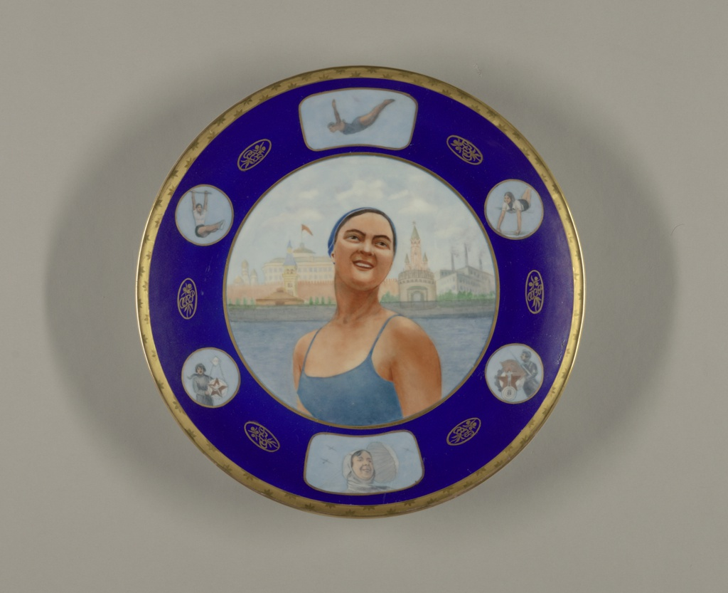 "Large, circular form; in center, image of smiling woman dressed in bathing suit and bathing cap, standing before skyline of Moscow; blue border with six reserves showing women athletes; between each reserve an oval medalion with ""USSR"" (in Russian) and floral motif; gilded border with burnished star-like pattern."