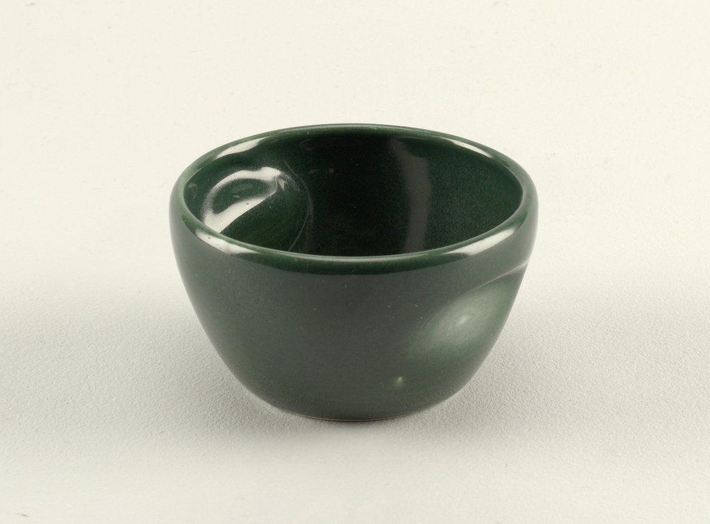 """Squat tapering circular form with circular mouth and two indentations in wall; """"spruce"""" green glaze."""
