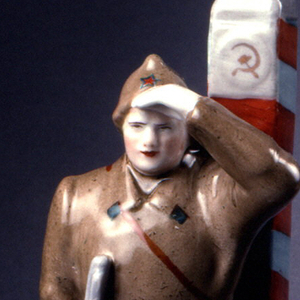 Red Army soldier stands with legs apart, leaning on post with hammer and sickle ornament, his left hand raised over his eyes, in his right hand a standing rifle, he wears long coat and hat; square base.