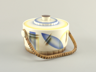 Round with stepped lid and faceted base. Round nobs on side to attach rattan handle. Bue and yellow abstract decoration.