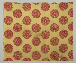 "Mustard yellow ground, printed in detached circular design of flower wreath framing leaf, in bright red. Design arranged in staggered rows, each element about 3 3/4"" across. Printing appears to be by block, superimposed on the yellow ground. Picotage around leaf. Both selvages present. Pieces of yellow 2/2 twill fabric used on the pieced side as part of the border."
