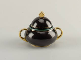 Two handled low bulbous bowl; handles in gold, foot in gold, mouth in turquoise and gold; hemispherical lid with cube in gold as finial.