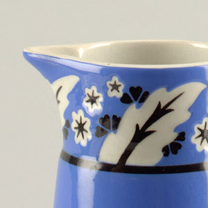 Tall, blue, cylinder body that slightly tapers towards the opening. The top rim is  decorated in a white and black floral pattern. The handle is also white.