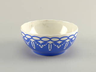 Deep circular bowl with a scalloped edge.  Interior and exterior glazed white with royal blue covering the majority of the exterior.  Near top, a white repeating design of stylized arrowheads, beaded garlands, and bands all surmounted by a chain of blue horizontal ovals.