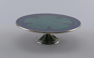 High footed cake plate in metal and earthenware decorated as though crackled in turquoise, with navy blue border and border of blue hearts and red dots.