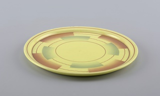 Circular plate with beveled edge and raised bottom rim.  Yellow background with straight and wavy brown lines forming concentric circles broken by semi-rectangular airbrushed swatches of brown and blue.