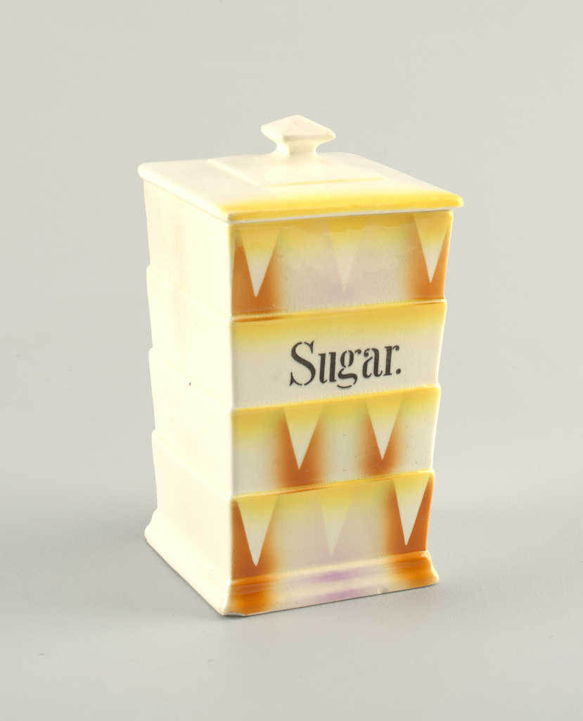 High rectangular box with shallow steps on all sides. Unpainted, except on one side, which shows atomized orange and yellow decoration and triangles. Stenciled text in black: Sugar. Square knob on lid.